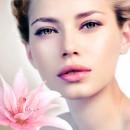 Девушка позирует в естественном макияже, рядом розовый цветок