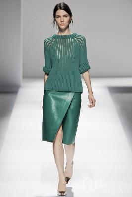 Модель в костюме зеленого цвета