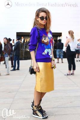 Девушка в золотой юбке и в вязаном свитере с мульт героем