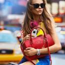 Яркая городская девушка с красной сумкой и в желтом топе