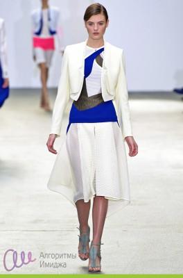 Модель демонстрирует ассиметричный наряд юбки, джемпера и жакета в контрастных цветовых сочетаниях молочного с синим и черным