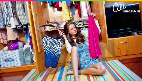 Молодая девушка разбирает одежду из своего гардероба сидя дома на полу