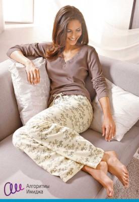 Девушка в домашней одежде пастельных тонов лежит на диване
