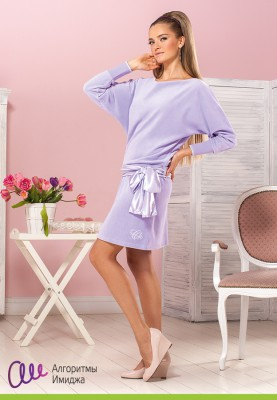 Девушка в сиреневом бархатном домашнем платье позирует в домашнем интерьере