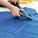 Закройщица режет ткань для пошива свитшота