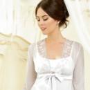 Девушка в белом прозрачном кружевном пеньюаре поверх белой ночной рубашки