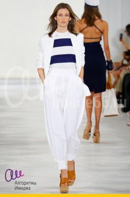 Модель демонстрирует на подиуме морской образ, сочетающий в себе белые брюки ижакет, дополненные топом в широкую синюю полоску