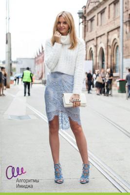 Девушка гуляет в модной кружевной юбке цвета сиренити и мягком вязаном белом свитере