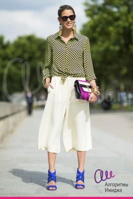 Девушка в ярком летнем образе, сочетает белые брюки-кюлоты и рубашку с принтом в клеточку