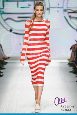 Модель демонстрирует на подиуме длинное силуэтное платье в красно-белую полоску