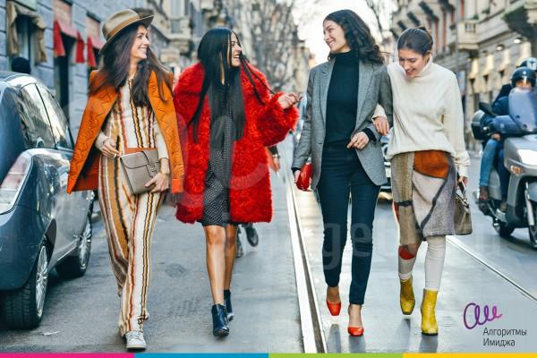 Девушки прогуливаются по дороге в демисезонной яркой одежде