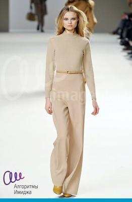 Модель демонстрирует монохромный бежевый наряд, где брюки имеют завышенную талию
