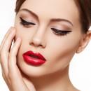 Модель демонстрирует распространенный макияж стрелки, красная помада