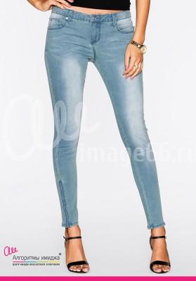 Девушка в серо-голубых джинсах скинни, черных босоножках и черной майке