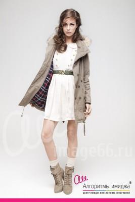 Девушка позирует в нежном белом платье и грубой куртке парке