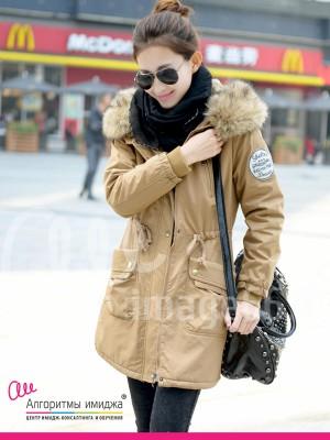 Девушка идет по городу в бежевой парке с мехом