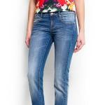 Модель демонстрирует голубые джинсы слим (slim) в сочетании с ярким разноцветным топом