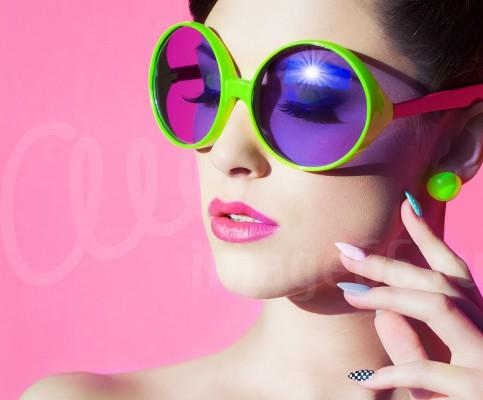 Девушка в солнцезащитных цветных очках на розовом фоне