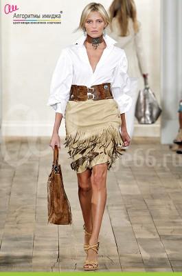 Девушка модель на подиуме в рубашке и юбке с широким ремнем