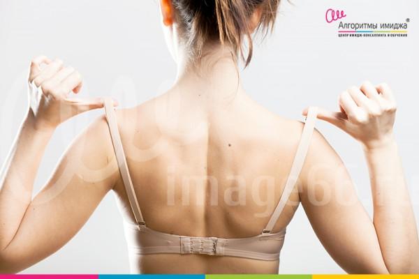 Девушка в бюстгалтере с оттянутыми лямками стоит к камере спиной