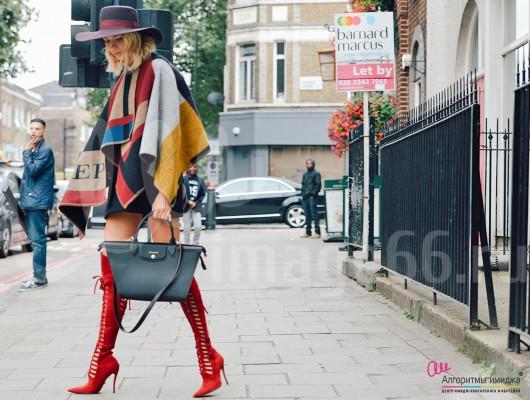 Стильная девушка в пончо, шляпе, красных сапогах и с сумочкой