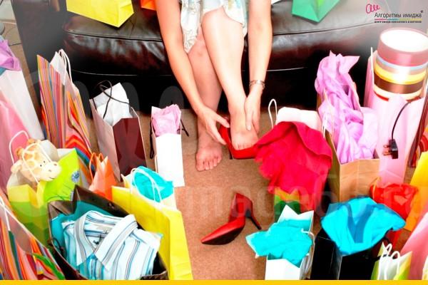 Девушка примеряет красные туфли среди множества пакетов из магазина