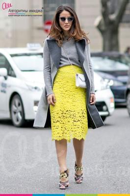 Стильная девушка в серой кофточке, сером пальто и желтой юбке