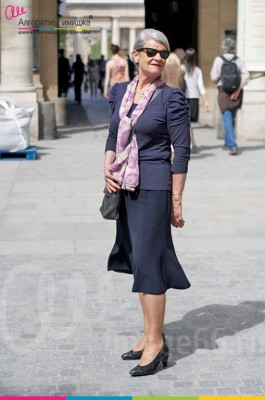 Элегантная женщина в  темной юбке  и жакете с ярким шарфом