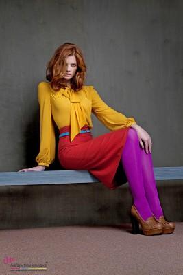Девушка, одетая в желтую блузку, красную юбку и фиолетовые колготы