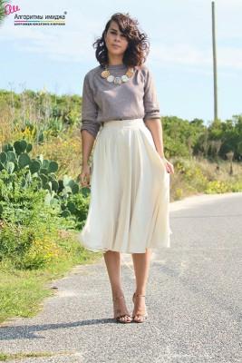 Девушка в светлой юбке-миди и сером свитере