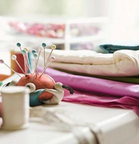 Ткани, нитки и иголки лежат на столе