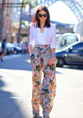 Девушка в струящихся летних брюках и блузке